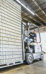Fork lift and driver loading a skid with beer cans