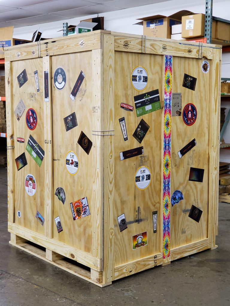 Crate we packed to ship our booth to show with stickers and keg collars all over it
